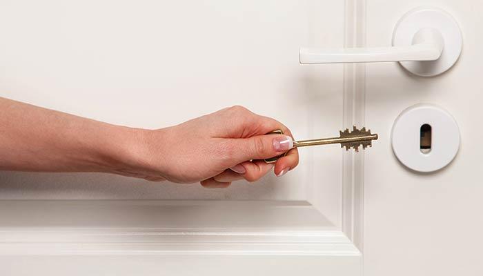 Personne ouvrant allant mettre un clé dans la serrure de sa porte à Lyon
